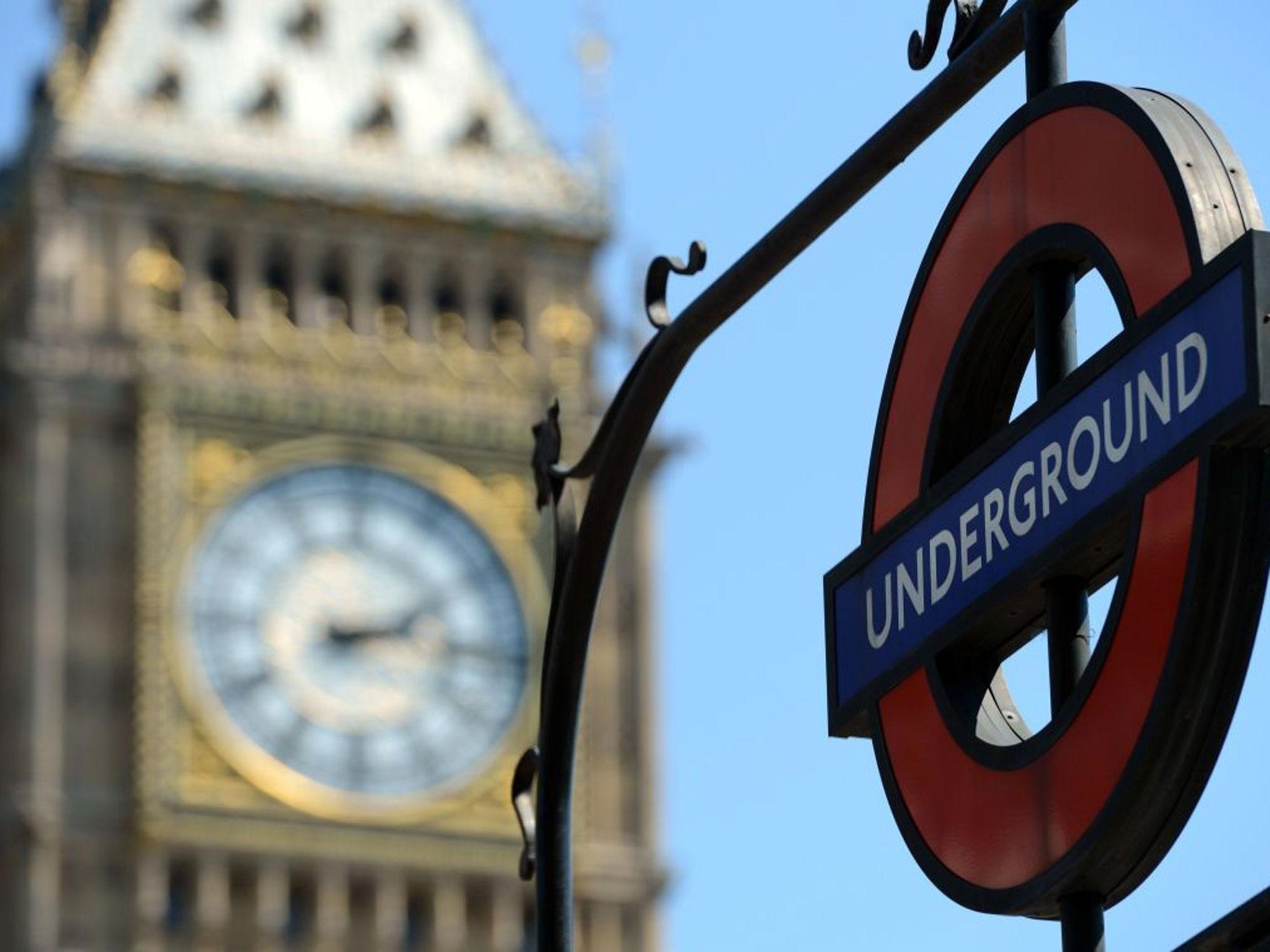 London underground sign next to Big Ben clock.